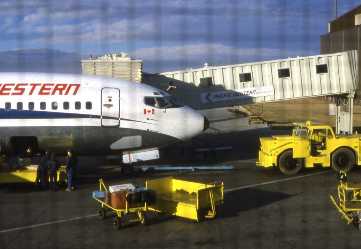 Lufthavn/Flyplass. Et fly fra Pasific Western, Canada,  parkert ved flyplassterminalen. Stor aktivitet ved flyet, inn eller utlasting.