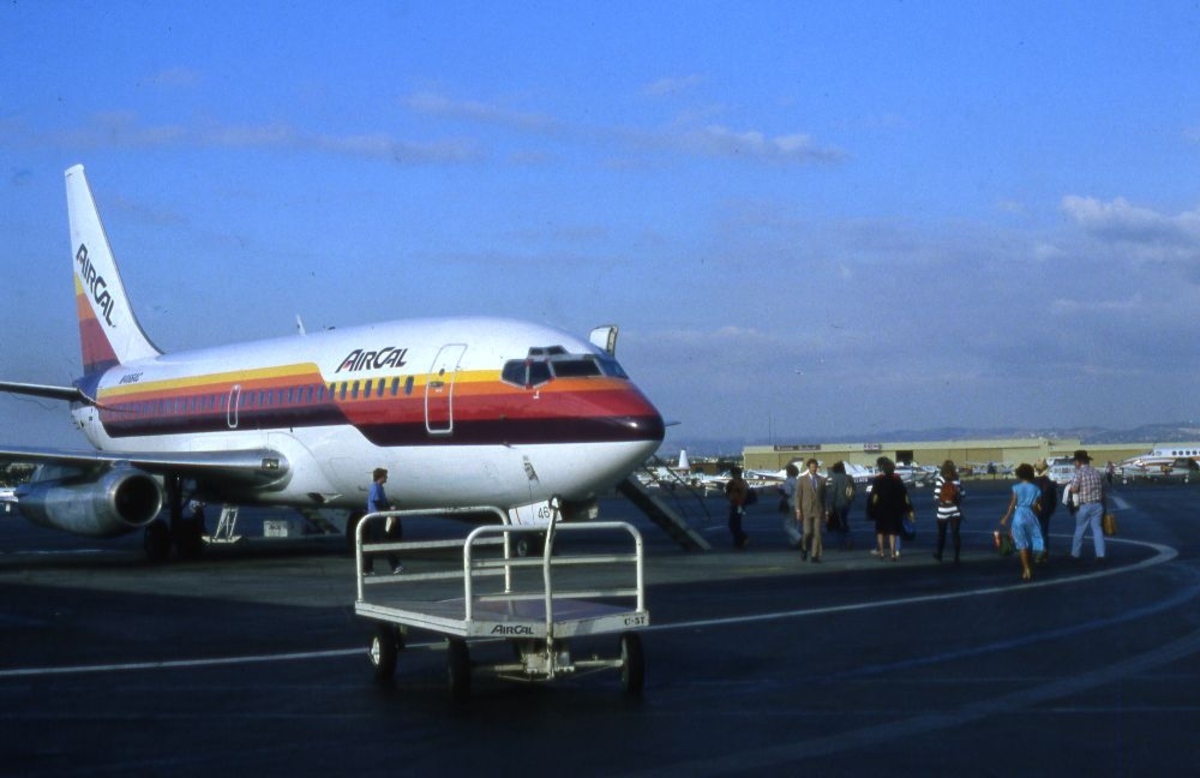Lufthavn/Flyplass. Et fly, Boeing 737 fra AIR CAL parkert. Passasjerer på vei til flyet for ombordstigning.