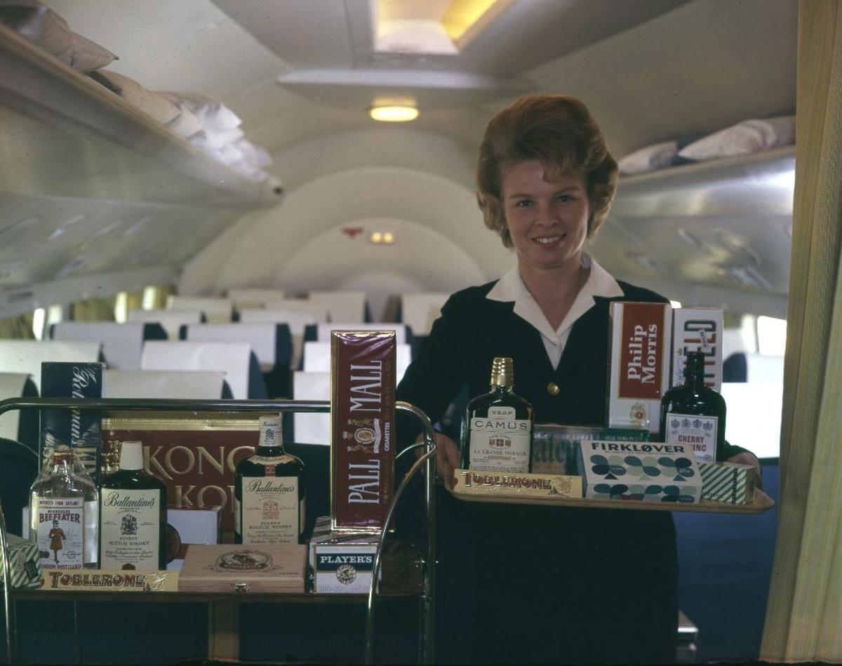 """Lufthavn/Flyplass. I et fly fra Braathens SAFE tilbyr en kabinansatt/flyvertinne stort utvalg av """"godterier"""" som kan kjøpes og nytes."""