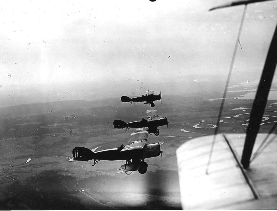 Luftfoto, tre fly i luften, Bristol Fighter. Landskap under. Litt av vinge og stag på ett fly, hvor bilde er tatt fra, i forgrunnen.
