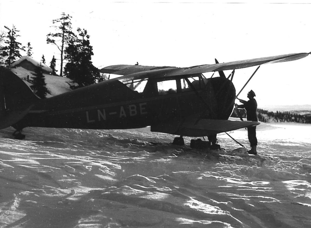 Åpen plass, ett fly med skiunderstell på bakken, Waco Cabin UIC4 LN-ABE.  en person foran flyet. Snø på bakken.