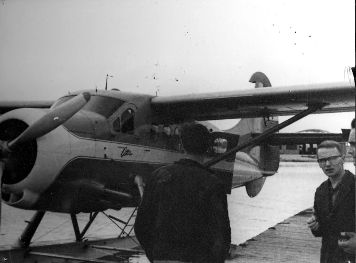 Sjøflyhavn, Skattøra.Tromsø.  Ett fly i vannkanten, De Havilland DHC 3 Otter fra Widerøes Flyveselskap  to personer i forgrunnen.