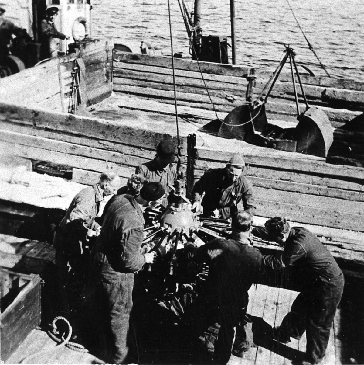 Havneområde. Noen personer ved en flymotor, for propell. Motoren henger i en heisekaran. Tilhører Junkers JU 52/3mge. Noe annet utstyr på kaia.