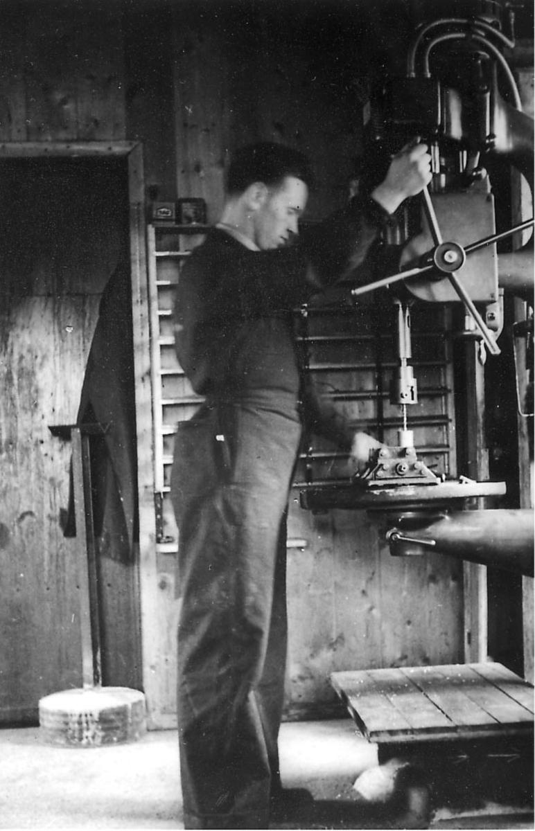 """Interiør fra verksted.  En person, verkstedarbeider/mekaniker, i arbeid ved """"borebenk""""."""