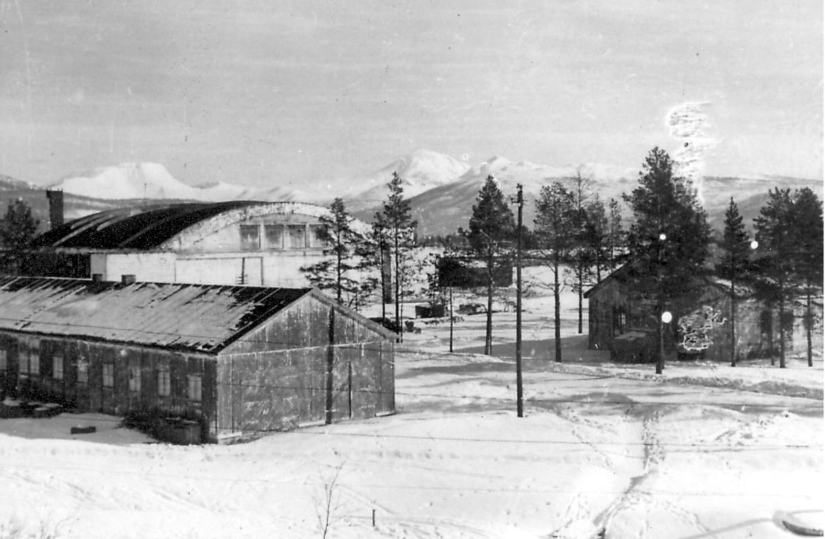 Noen bygninger. Muligens verksteder og hangar for oppbevaring og ettersyn av fly? Snø på bakken.