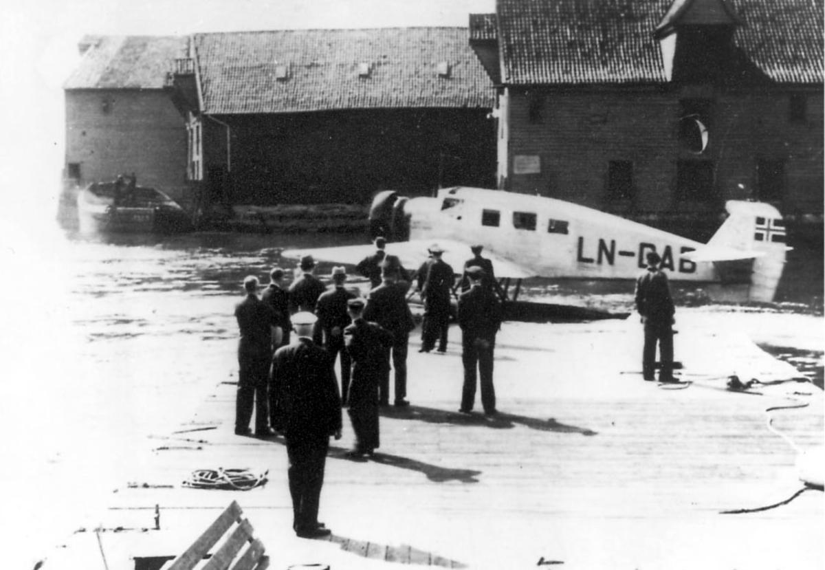 """Ett fly på bakken, Junkers Ju W 34 LN-DAB  """"Ternen"""".Flere personer ved flyet. Brygger - bygninger i bakgrunnen"""