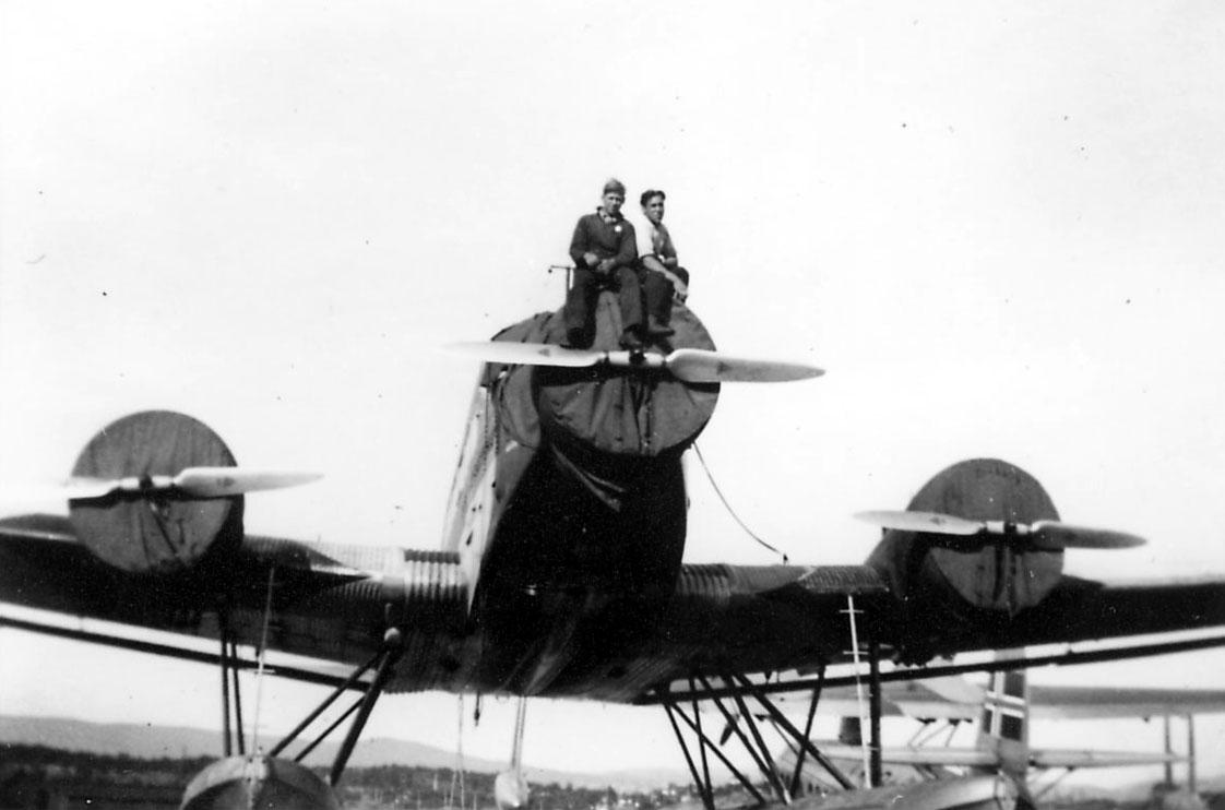 Lufthavn, ett fly på bakken, Junkers Ju 52/3mg2e. Motorene dekket med presenninger. to personer sitter på en av motorene. Litt av ett annet fly sees i bakgrunnen.LN-DAG Sikorsy S-43. fra DNL
