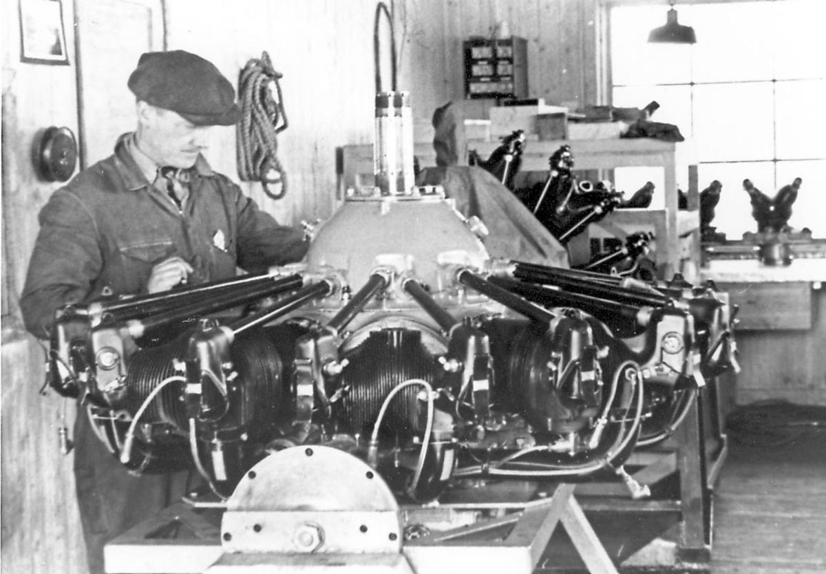 Interiør, inne i verksted. en person, ettersyn på  flymotor for propelldrift. Motoren tilhører Junkers Ju 52/3mg3e.