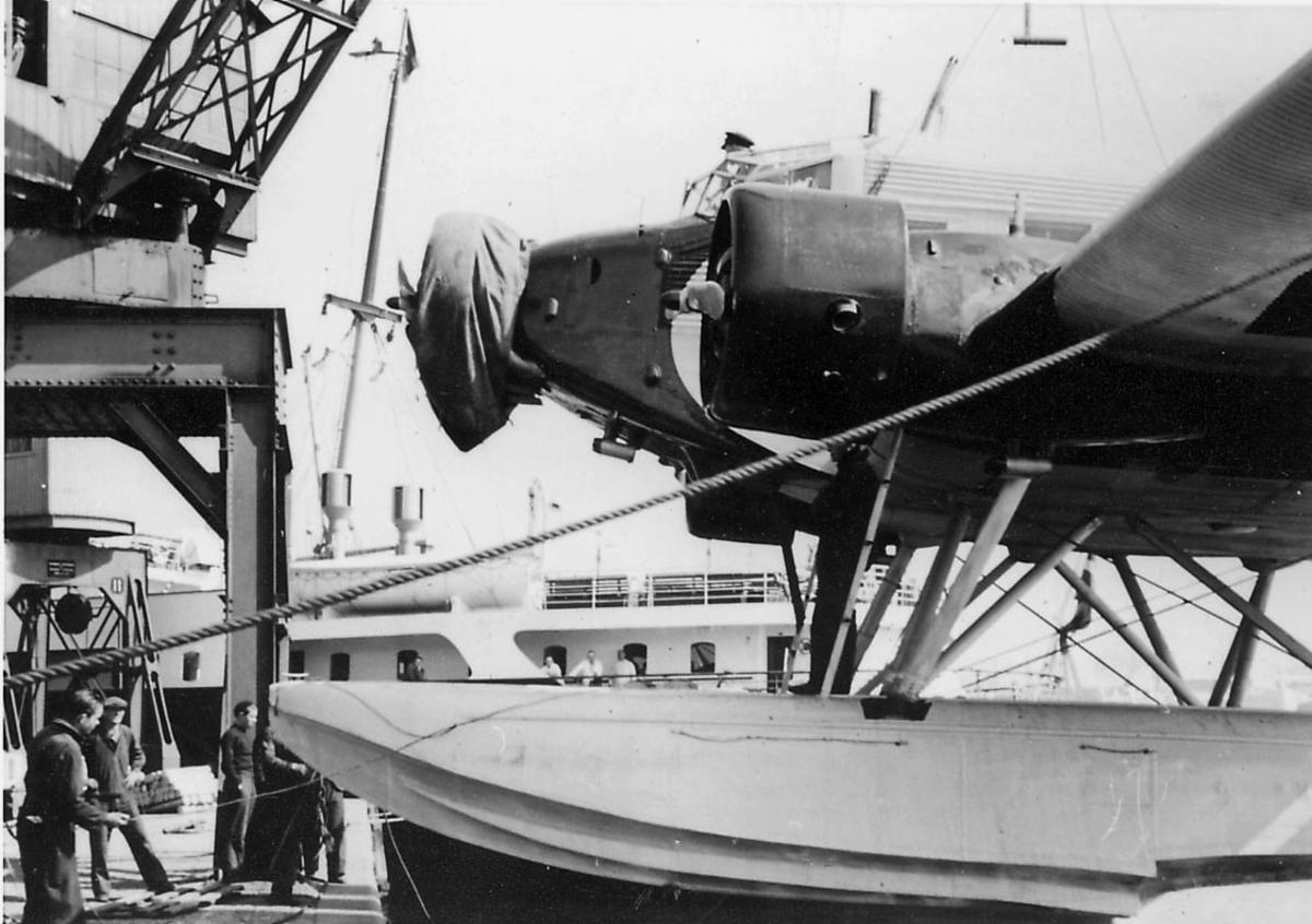 Ett fly, Junkers Ju 52/3mg3e, henger i en heisekran. Flere personer ved flyet. Litt av overbygg på en båt i bakgrunnen.