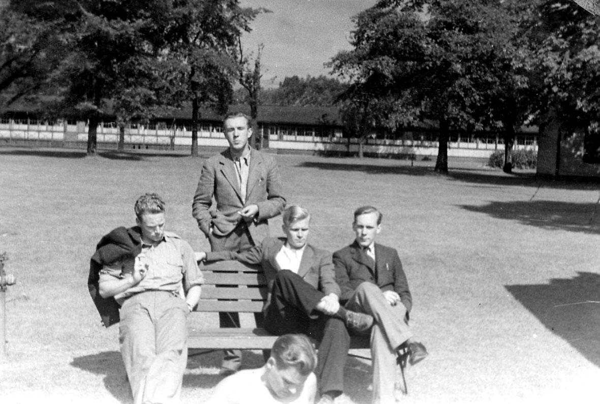 Portrett, fem personer ved en benk i en park.