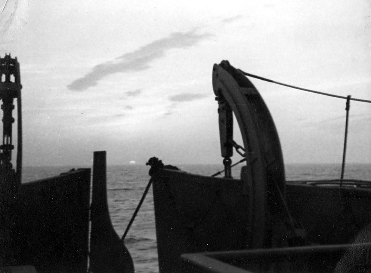 Ombord i fartøy. Litt av livbåtene sees. Hav med sola like over horisonten i bakgrunnen.