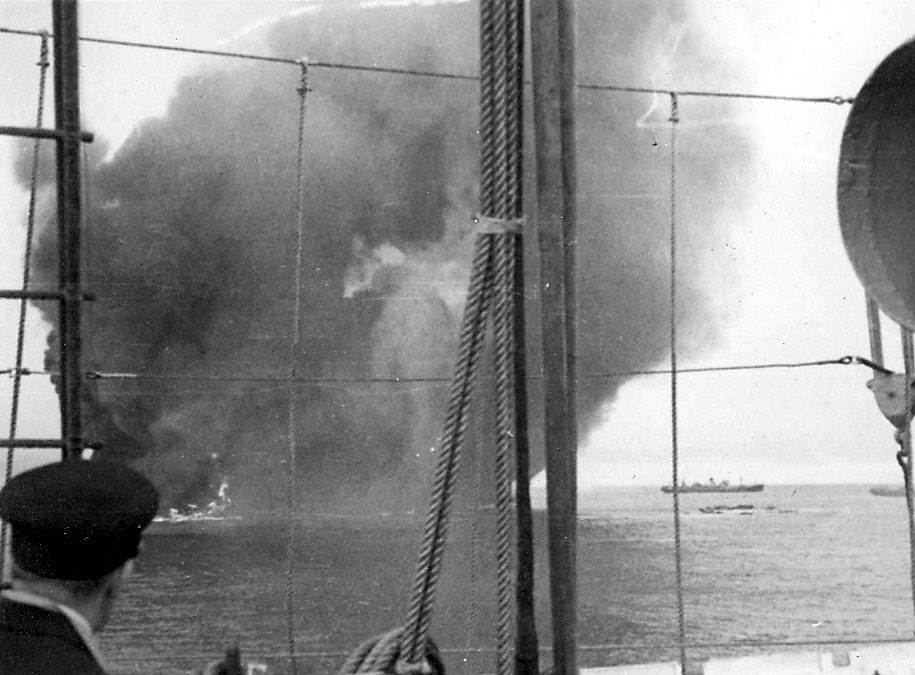 Flere fartøy på åpent hav. Stor røyksky satiger opp, ant. etter bombeangrep. Bildet tatt fra annet fartøy, hvor en person i militæruniform står med rygget i mot.