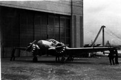 ett fly på bakken, skrått forfra, foran bygning, ant. hangar
