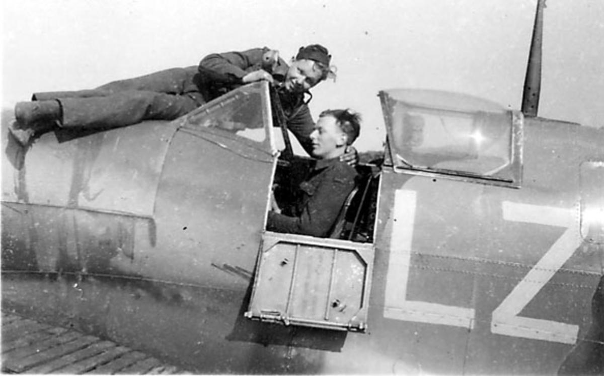 Fly sett fra siden, cockpit. Bokstavene LZ på siden. 2 personer, militære, i uniform, den ene sitter inne i cockpit, den andre ligger på flyskroget foran. Spififire Mk5