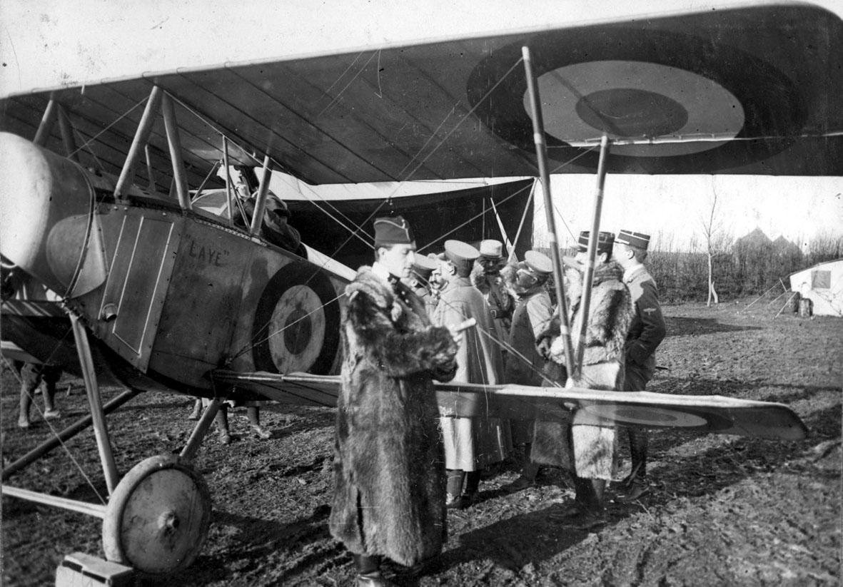 Fly, Nieuport 11C.1. Skrått forfra. Står på bakken. Flere personer ved flyet.