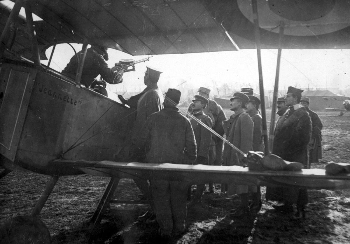 """Fly, Nieuport 11C.1 """"Jeanette"""", på bakken. Skrått forfra, midtpartiet. Flere personer ved flyet. 1 person i cockpit, """"justerer"""" påmontert våpen, maskingevær."""