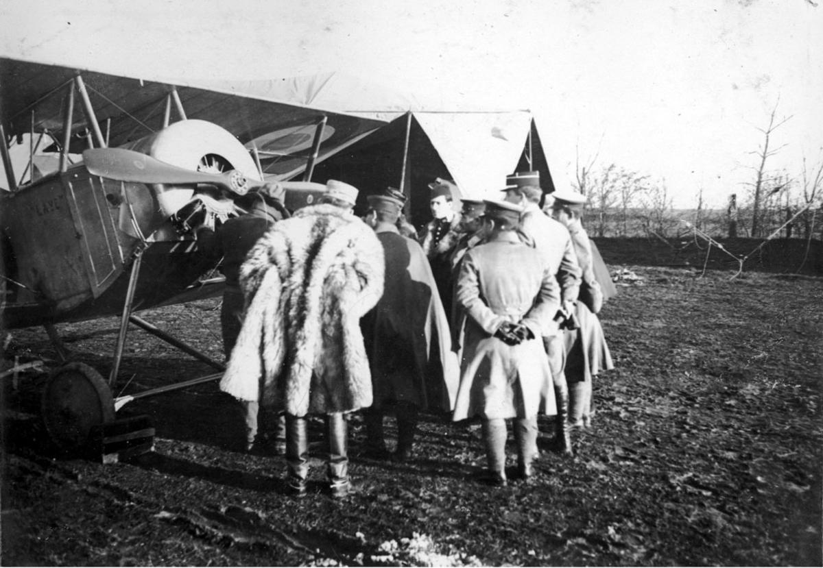 """Fly, Nieuport 11C.1 """"Laye"""". Skrått forfra, forpartiet.Står på bakken. Flere personer ved flyet. Bygninger - hangarer bak, (telt?)"""