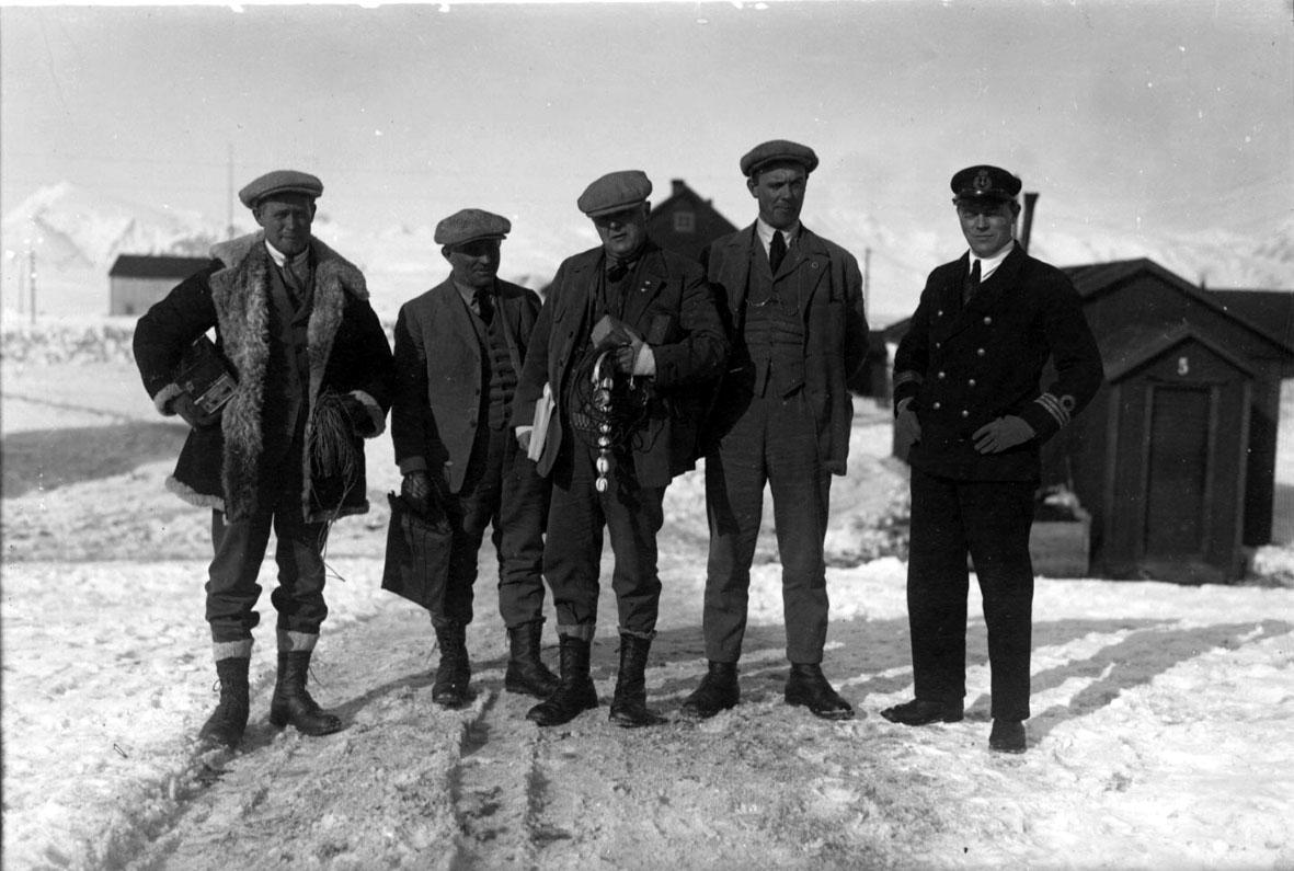 """4 personer fra luftskipet """"Norge"""" like før avgang, og Orlogskapteinen på """"Heimdal"""".  Bygninger bak, snø på bakken."""