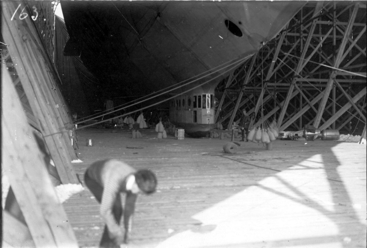 """Luftskipet """"Norge"""" fortøyd inne i luftskiphangaren. Underskiden av luftskipet og gondol sees. En person står bøyd, i forgrunnen"""
