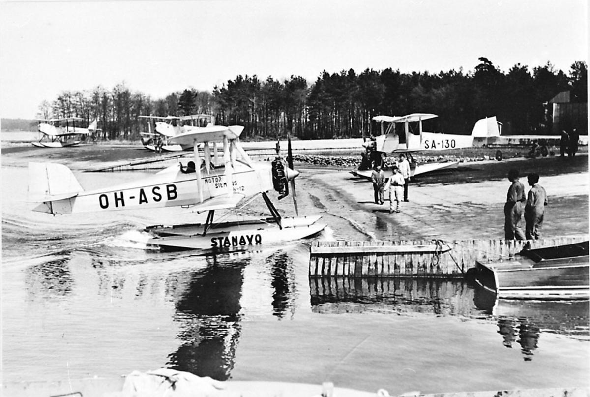 Fly, propellfly, dobbeldekker, Sääski OH-ASB, foran. Sjøflyhavn med flere sjøfly. Noen personer.