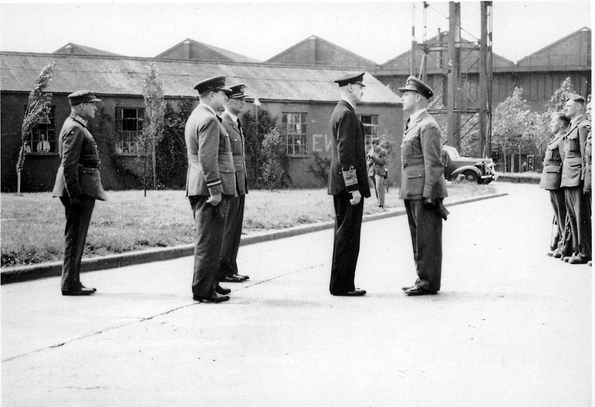 Kong Haakon VII i samtale med offiser. Kronprins Olav t.h. T.v. sees noen soldater, i militæruniform, oppstilt. Bygninger bak.