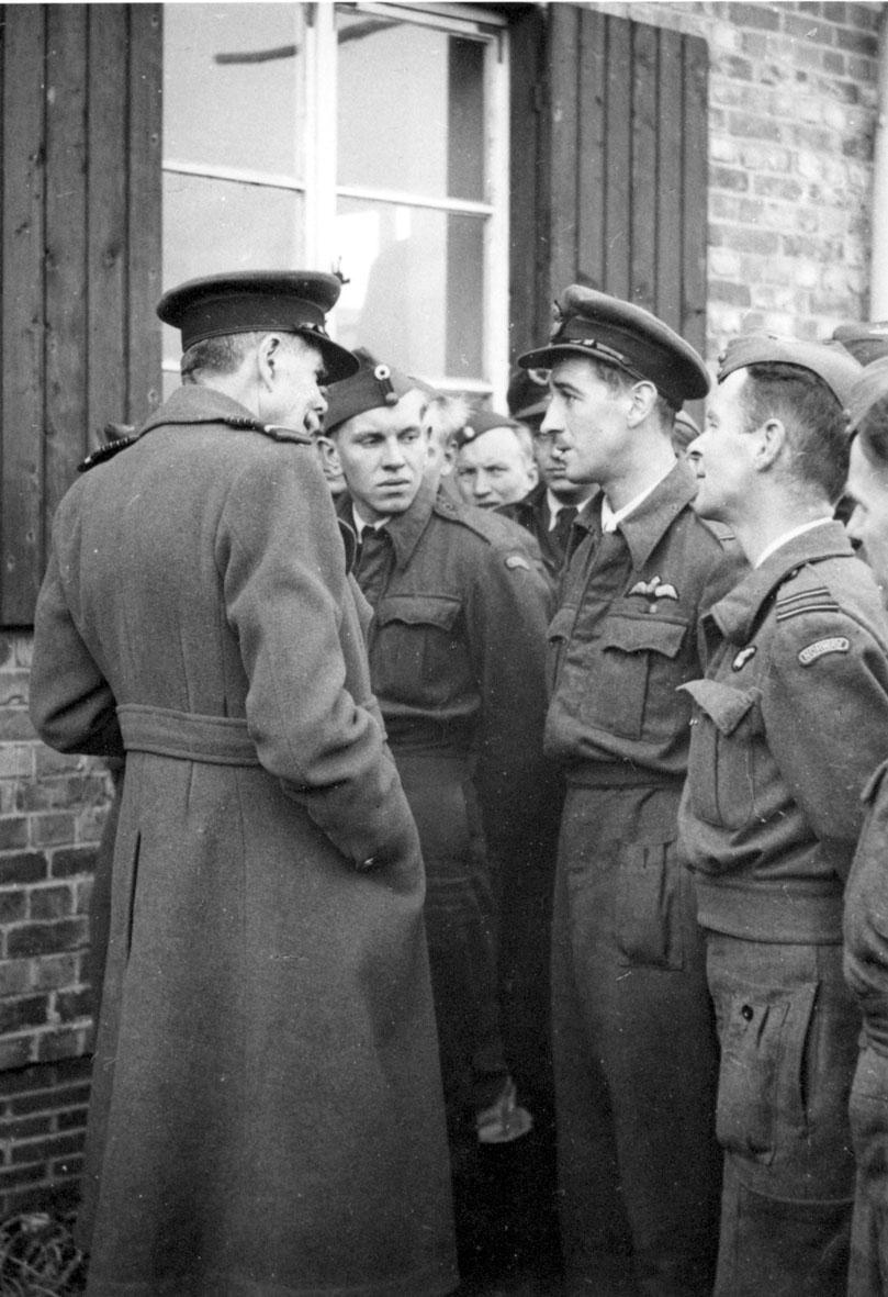 En gruppe personer i militæruniform. Offiserer og soldater (piloter) foran bygning.