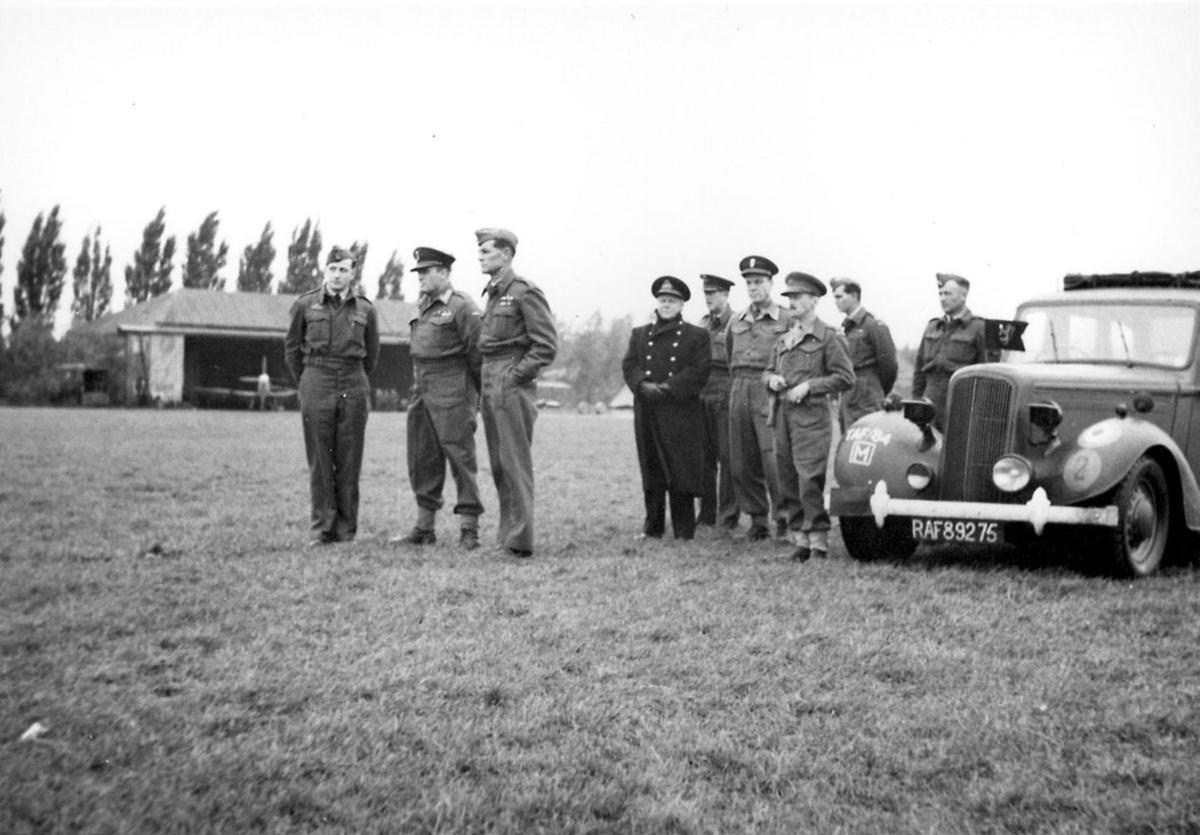 En gruppe personer i militæruniform, tatt utendørs. Kronprins Olav og en gruppe personer. T.h. bil med regisrering RAF 89275. Bak sees et fly inne i en hangar.