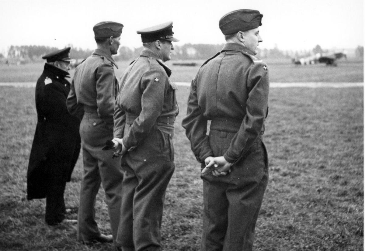 4 personer i militæruniform. Kronprins Olav og 3 andre på en åpen plass, med flere fly i bakgrunnen.