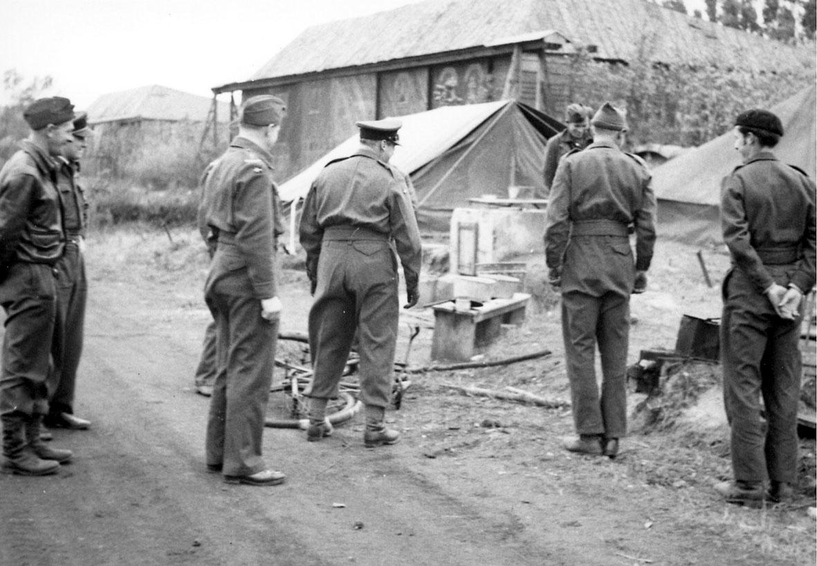 8 personer i militæruniform. Kronprins Olav og 7 andre. En sykkel og div. i bakgrunnen, bygning og telt.