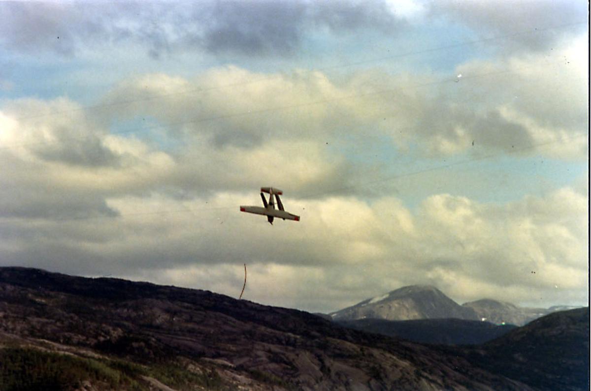 Sjøfly, enmotors propellfly, Cessna 206, henger fast i høyspentledning over en fjord.
