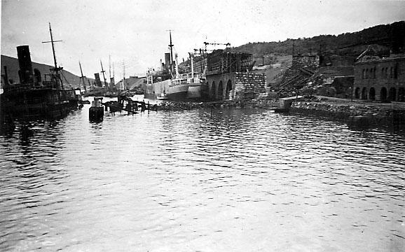 Havneområde, flere fartøy ligger delvis nedsunket og ødelagt. Ruiner inne på land.