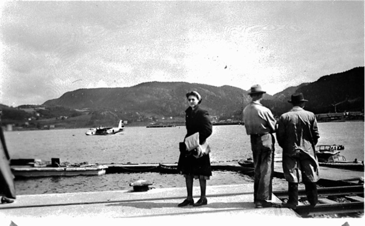 """Kai med 3 personer i forgrunnen. Bak ligger et fly i bøye, Short S.25 Sunderland, LN-IAU """"Bamse Brakar"""", fra DNL. Sett fra siden."""