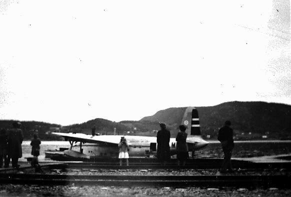 """Åpen plass foran med jernbanespor. Noen personer. Bak ligger et fly ved kai, Short S.25 Sunderland, """"Bamse Brakar"""", fra DNL. Sett fra siden."""