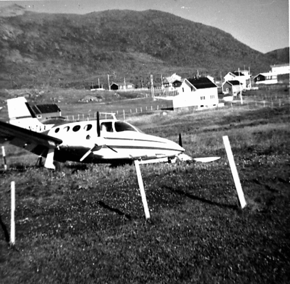"""Fly, Cessna 401A, LN-TVX. Skrått forfra. """"Ligger"""" ute på et jorde. Ene vingen nede i bakken. Bygninger bak."""