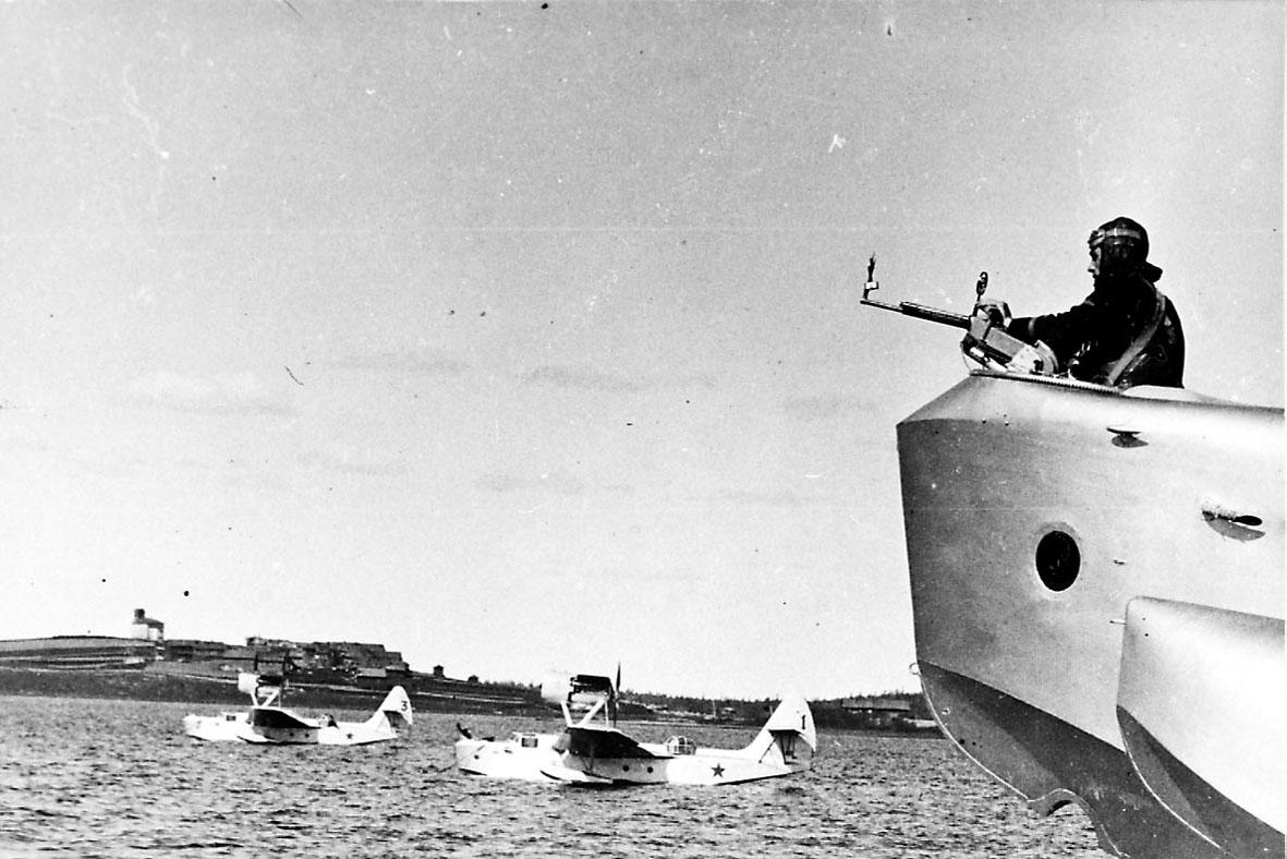 2 fly, MBR-2, ligger stille på havoverflata sett fra siden. I forgrunnen sees forparten på et tredje fly, MBR-13, med en person og maskingevær. Noen bygninger inne på land i bakgrunnen.