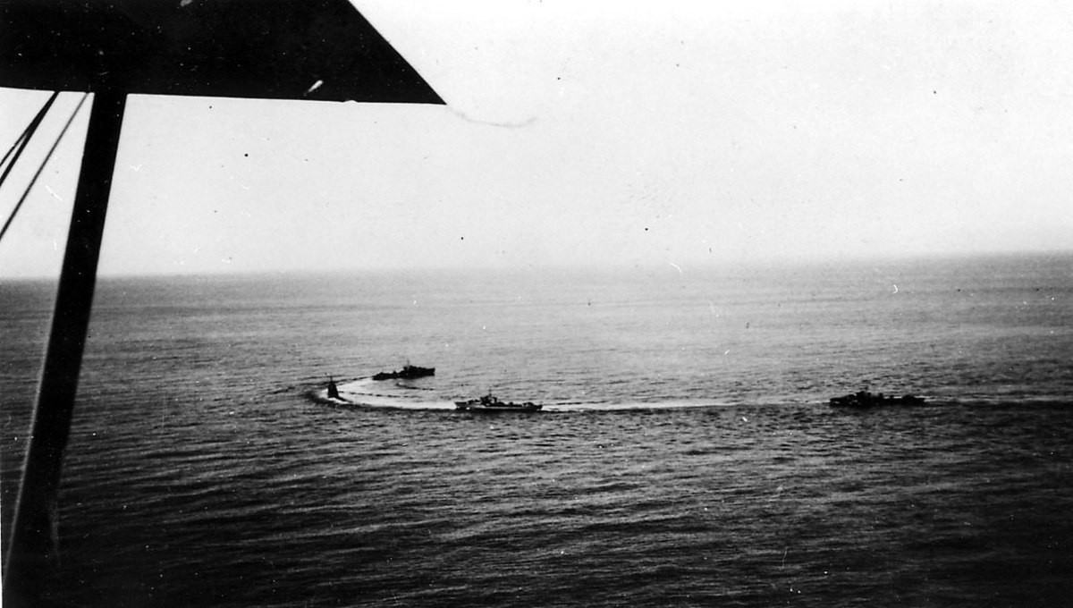 Luftfoto, litt av ene vingen på flyet bildet er tatt fra sees. Under sees 3 militærfartøy,  i fart på havoverflata.