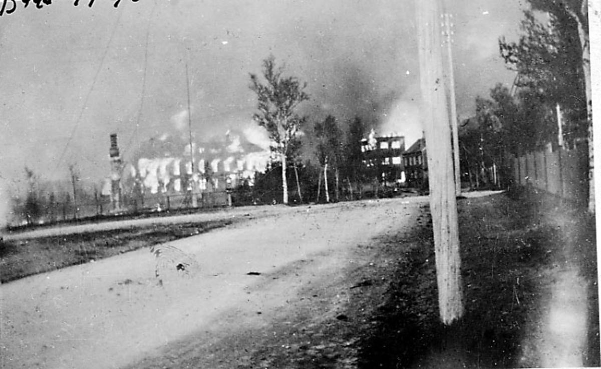 Ruin av bygning, Middelskolen/Handverkeren i brann. Bodø etter bombingen under 2. verdenskrig. Vei i forgrunnen.