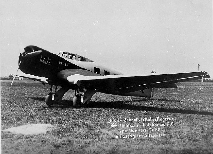 """1 fly på bakken, Junkers JU 60 """"Pfeil"""" fra Lufthansa. Skrått forfra. Står ute på åpen gresskledt plass."""