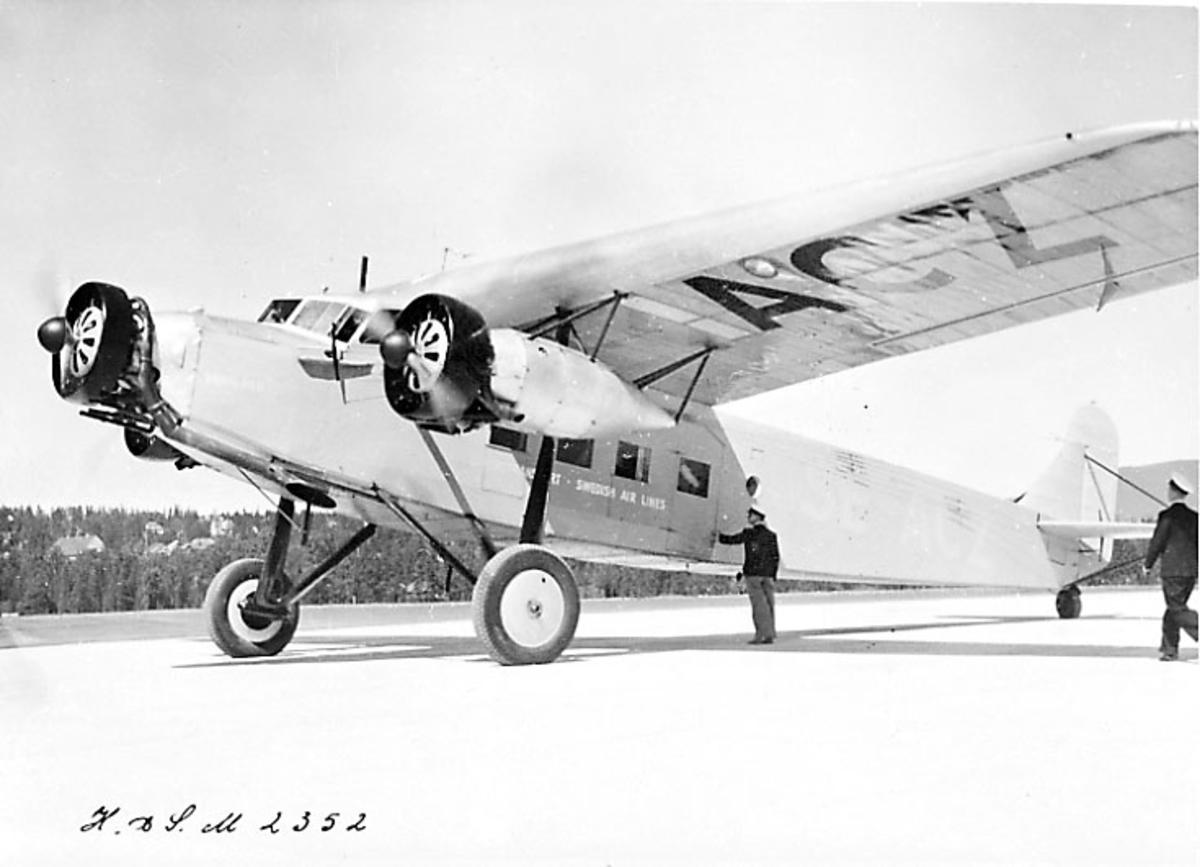 """Lufthavn, 1 fly på bakken. Fokker F.XII SE-ACZ """"Varmland"""" fra Swedish AB Aerotransport. Sett fra siden. 2 personer i flyuniform ved flyet."""