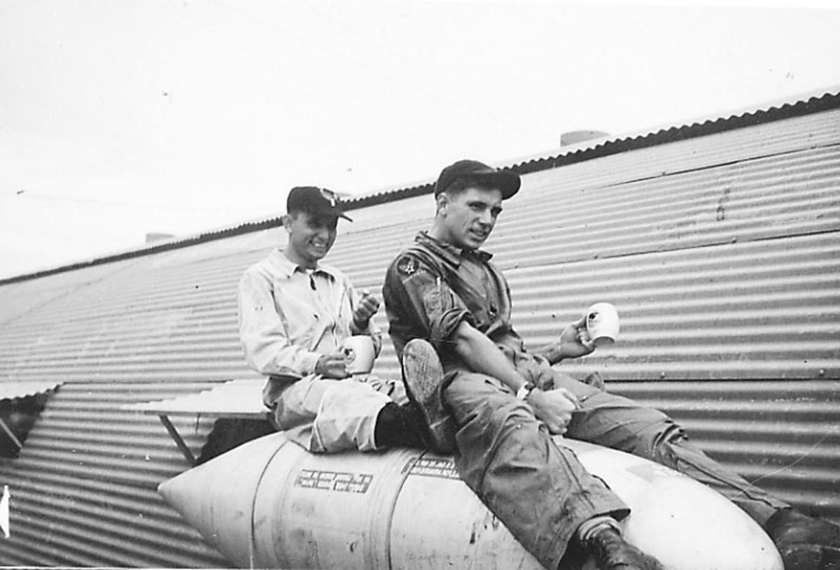 Portrett, 2 personer sitter på sprenglegeme/bombe.