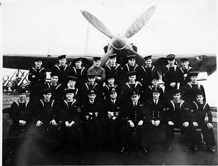 Portrett, gruppefoto av personer i militæruniform. 1 fly i bakgrunnen, Baracuda.
