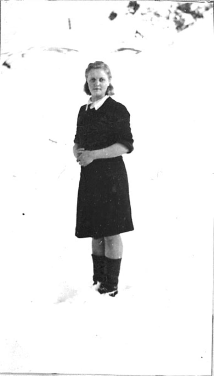 Portrett, 1 person - ung kvinne ikledd kjole - oppstilt. Tatt utendørs. Snø på bakken.