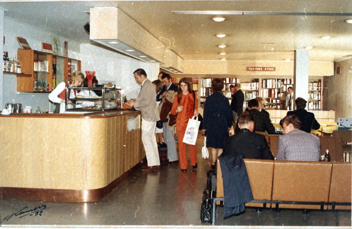 Lufthavn, inne i kafeteria. Flere personer.