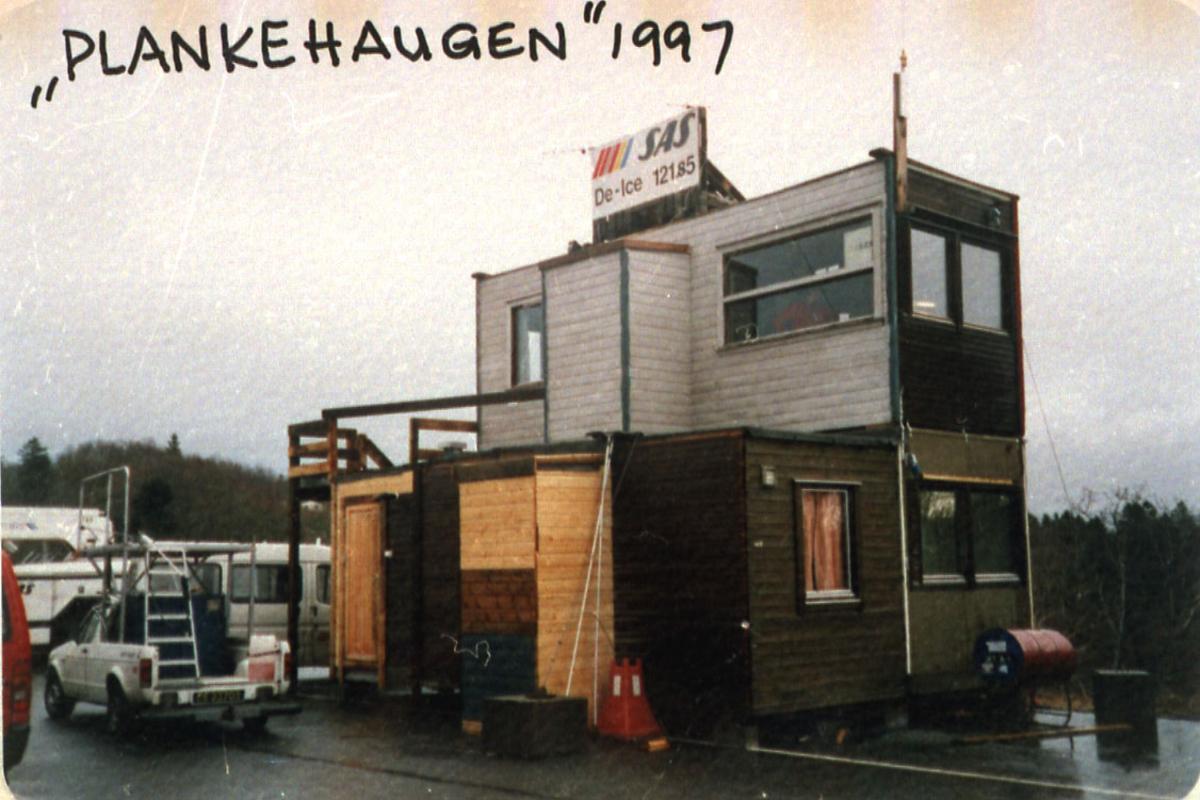 Lufthavn, 1 bygning i forgrunnen. Kjøretøyer og div utstyr bak.