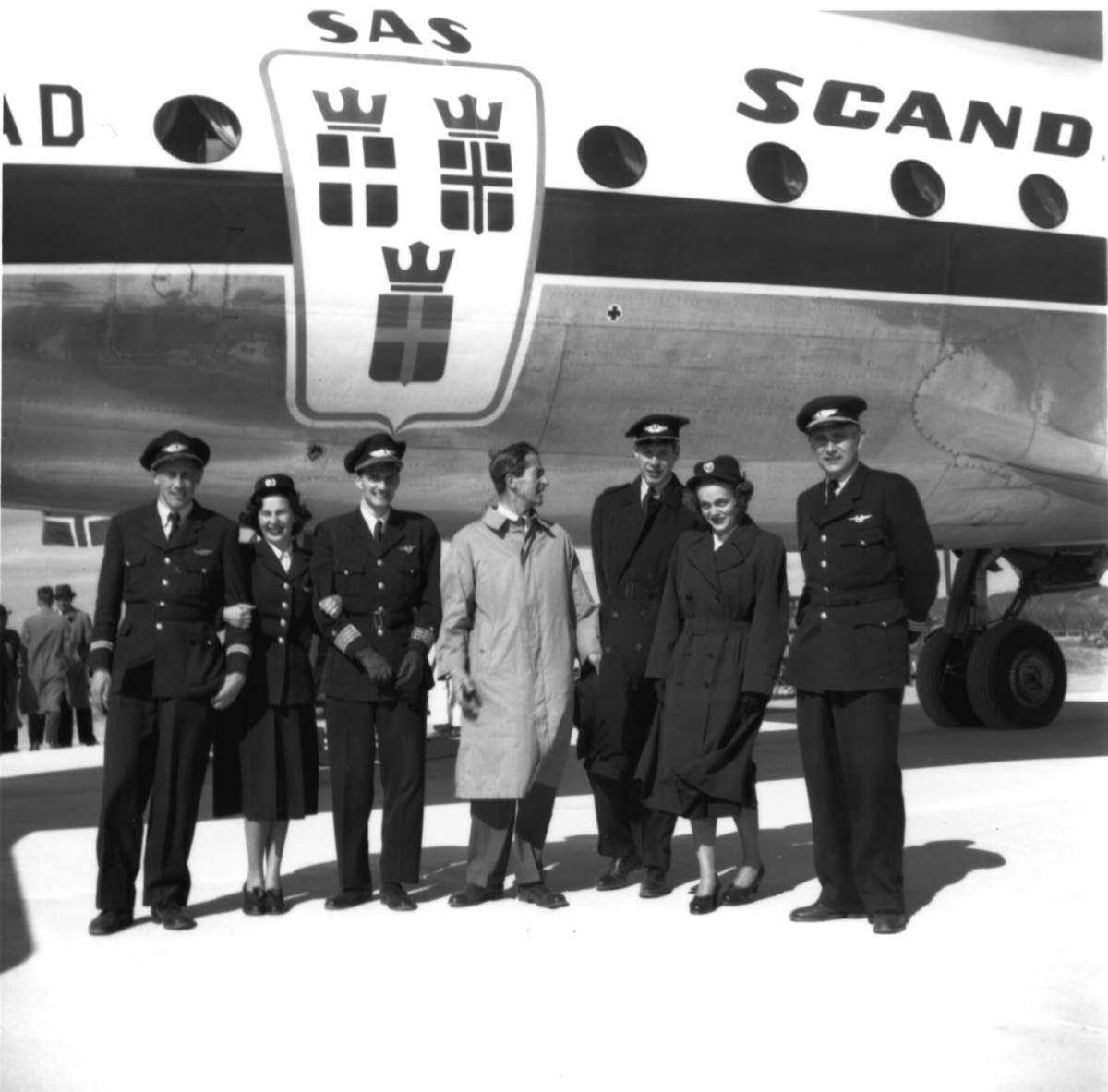 """Lufthavn, flere personer oppstilt foran ett fly, DC-4 Skymaster LN-IAD fra SAS. Flypersonell i uniformer og en person i """"vanlige"""" klær."""