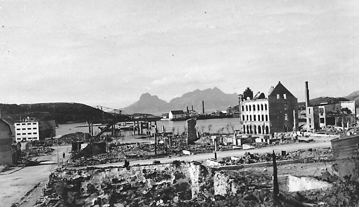 Tettsted/by. Bygninger i ruiner. Havneområde i bakgrunnen.