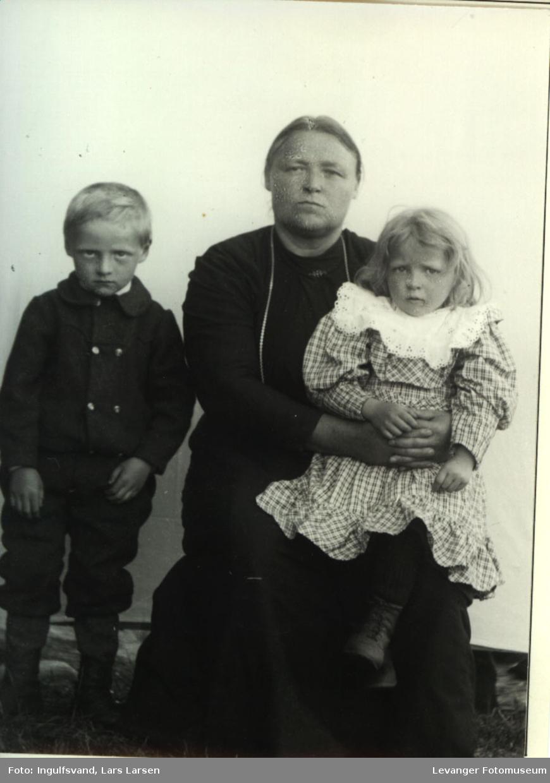 Gruppebilde av en kvinne og to barn, jente og en gutt.