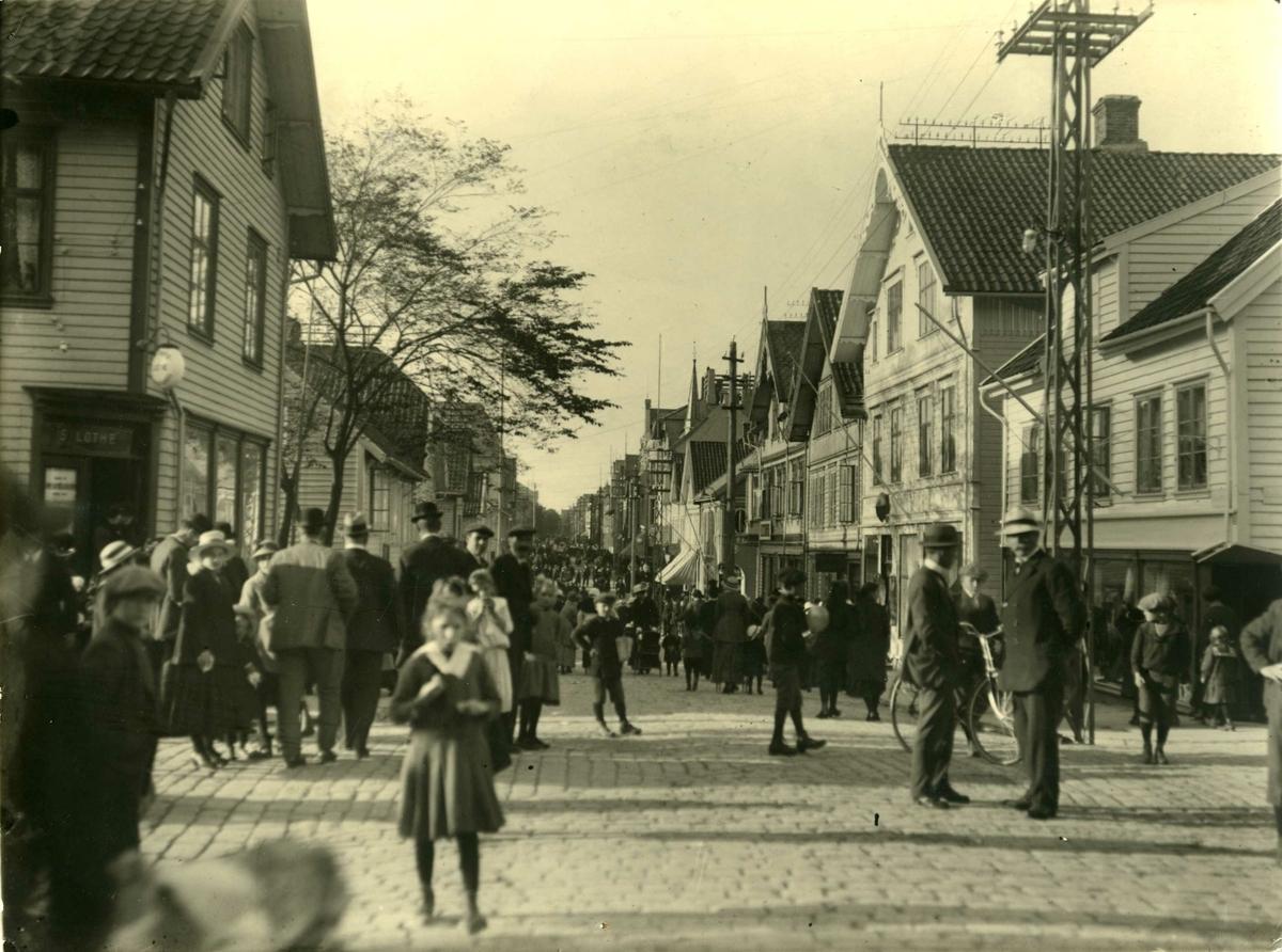 Prikkedag, Mikeli (29. sept.?) 1916. S. Lothes bokhandel på hjørnet (gatekrysset Haraldsgt./Kaigt.). Mange mennesker samler. Brosteinbelagt gateløp.