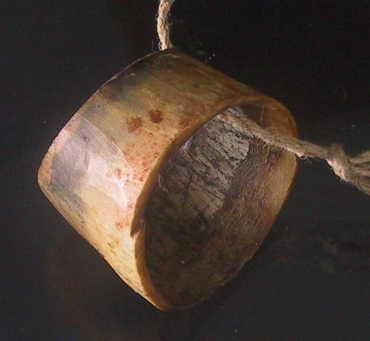 Pølsehorn, laget av kuhorn.  Liten, gul og sortflekket, avsmalnende  bredde.   Form som serviettringer.  Åpning oval