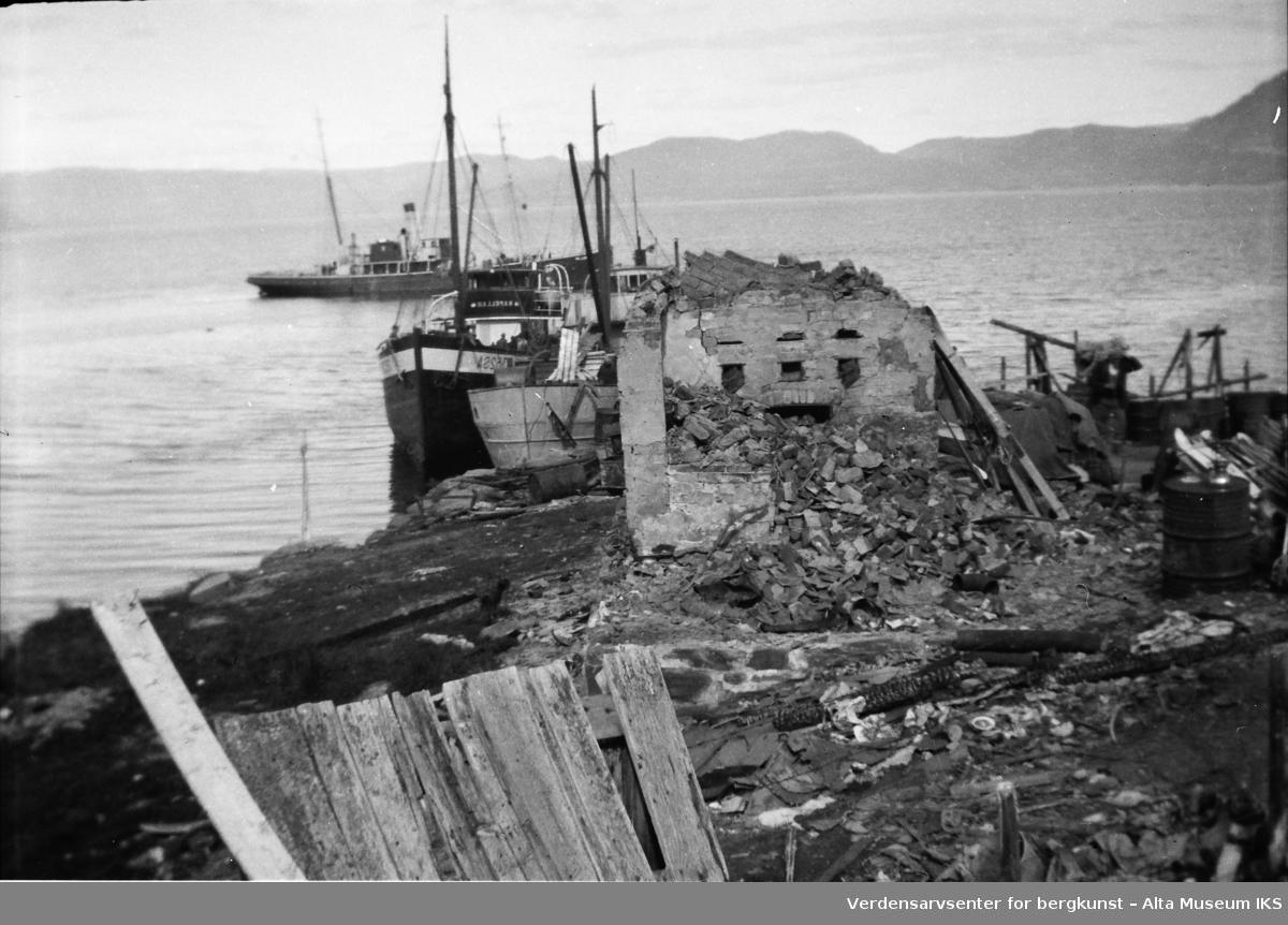 Ruiner etter krigen ved havet, og båter som prøver å legge til. Bildet er tatt i 1945